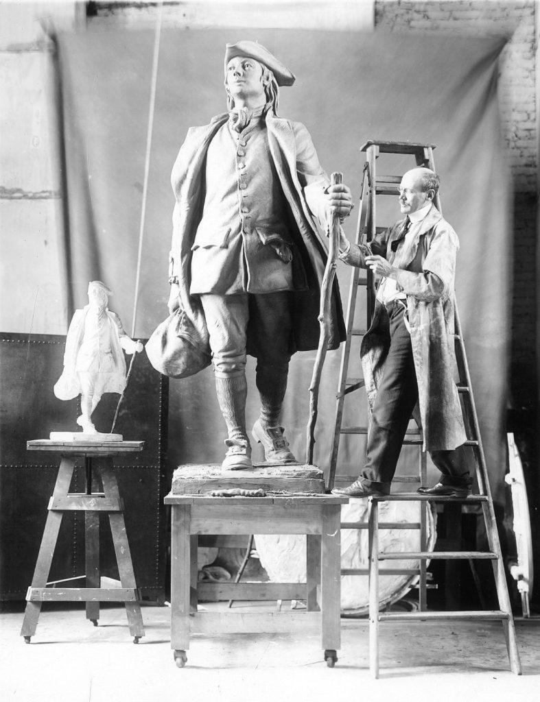 R. Tait (Robert Tait) McKenzie at work in his studio on his sculpture of young Benjamin Franklin, 1911