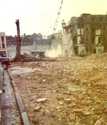 East side of 200 block of South McAlpin Street, 1960, showing land recently cleared on McAlpin Street and demolition-in-progress on the south side of 3600 Walnut Street. In the background are the buildings on the north side of Walnut Street, the three-story 3625 Walnut Street at the extreme left margin and the one-story, commercial garages at 3613-23 Walnut at center left.