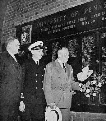 Thomas Sovereign Gates (Penn President, 1930-1944) places a wreath at base of War Memorial plaque in Furness Library portico, part of 1945 Alumni Day ceremonies, 1945