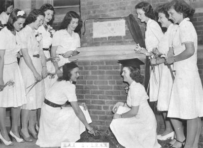 Women planting ivy next to brick wall with plaque