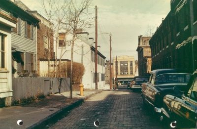 200 block of South McAlpin Street, 1959. View toward north, with 3625 Walnut Street in the background, at center right. At the center of the photograph is the three-story, whitewashed stone exterior of the Faculty Club, at 204-210 South McAlpin. Immediately to its left, behind a row of hedges at 212 South McAlpin, is the Delta Delta Delta sorority house. Just visible on the right margin is the doorway of the Alpha Mu Pi Omega medical fraternity house at 215 South McAlpin.